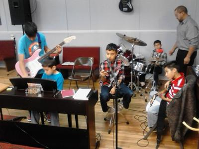Kids practicing in church Josh is the one standing with the guitar, by the piano.